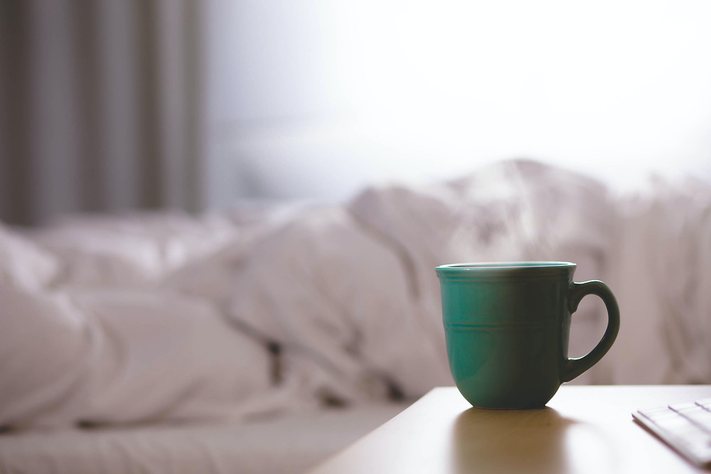 Cup of steaming tea or coffee next to a bed