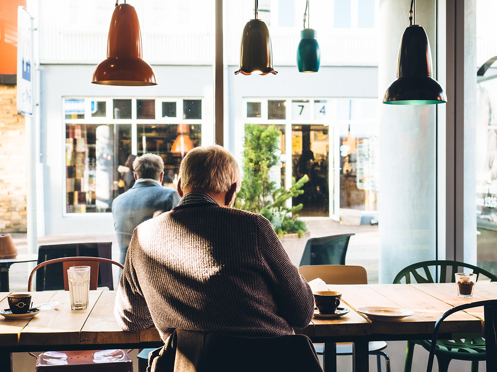 Older man sitting in a cafe writing notes, with his back to the camera