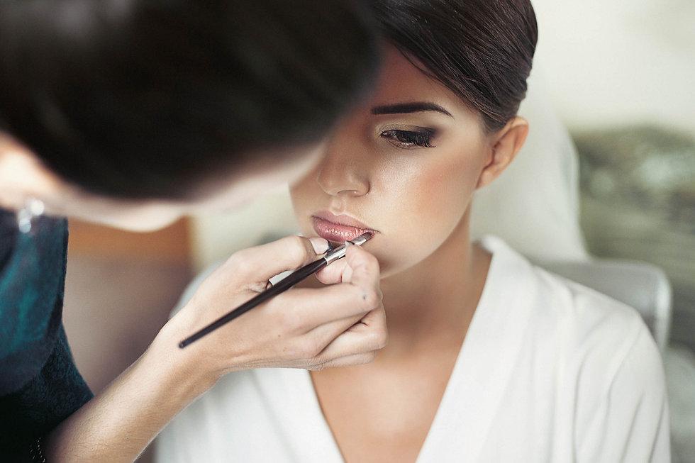 makeup artist makes young beautiful brid