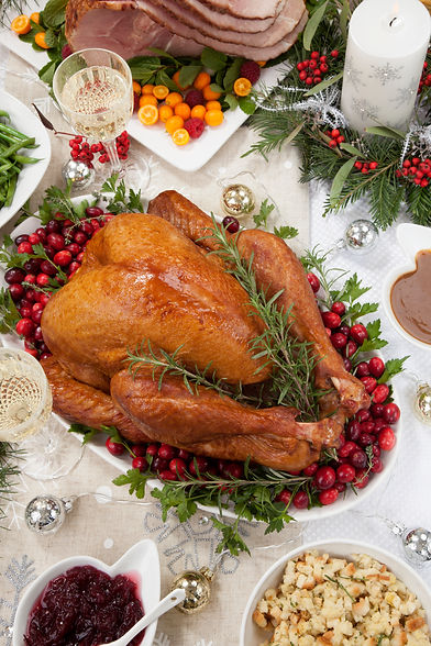 Smoked turkey on a tray garnished with fresh cranberries and herbs, roasted ham, side dish