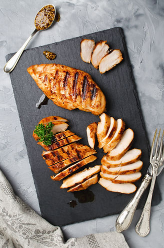 Grilled chicken fillets on slate plate. Gray concrete background.jpg