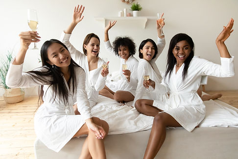 Portrait happy diverse girls wearing white bathrobes holding champagne glasses, sitting on