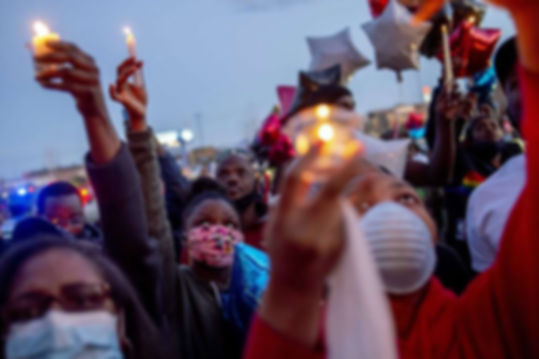 Family and friends lift their candles to