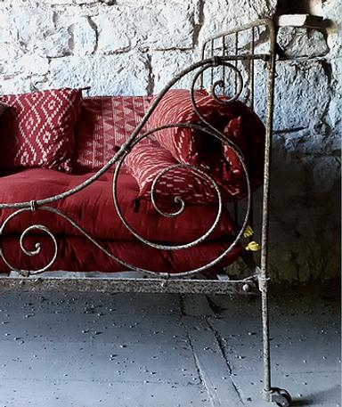 Banquette de jardin ancienne agrémenté d'un matelas et de coussins imprimés handblock