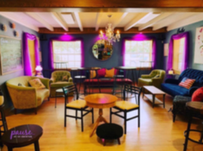 Our lounge at Pause... colorful couches and high tops, a chandelier, eclectic style, brigt winow.