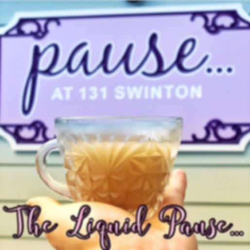 hand holding a crystal cup of kava in front of outside Pause sign