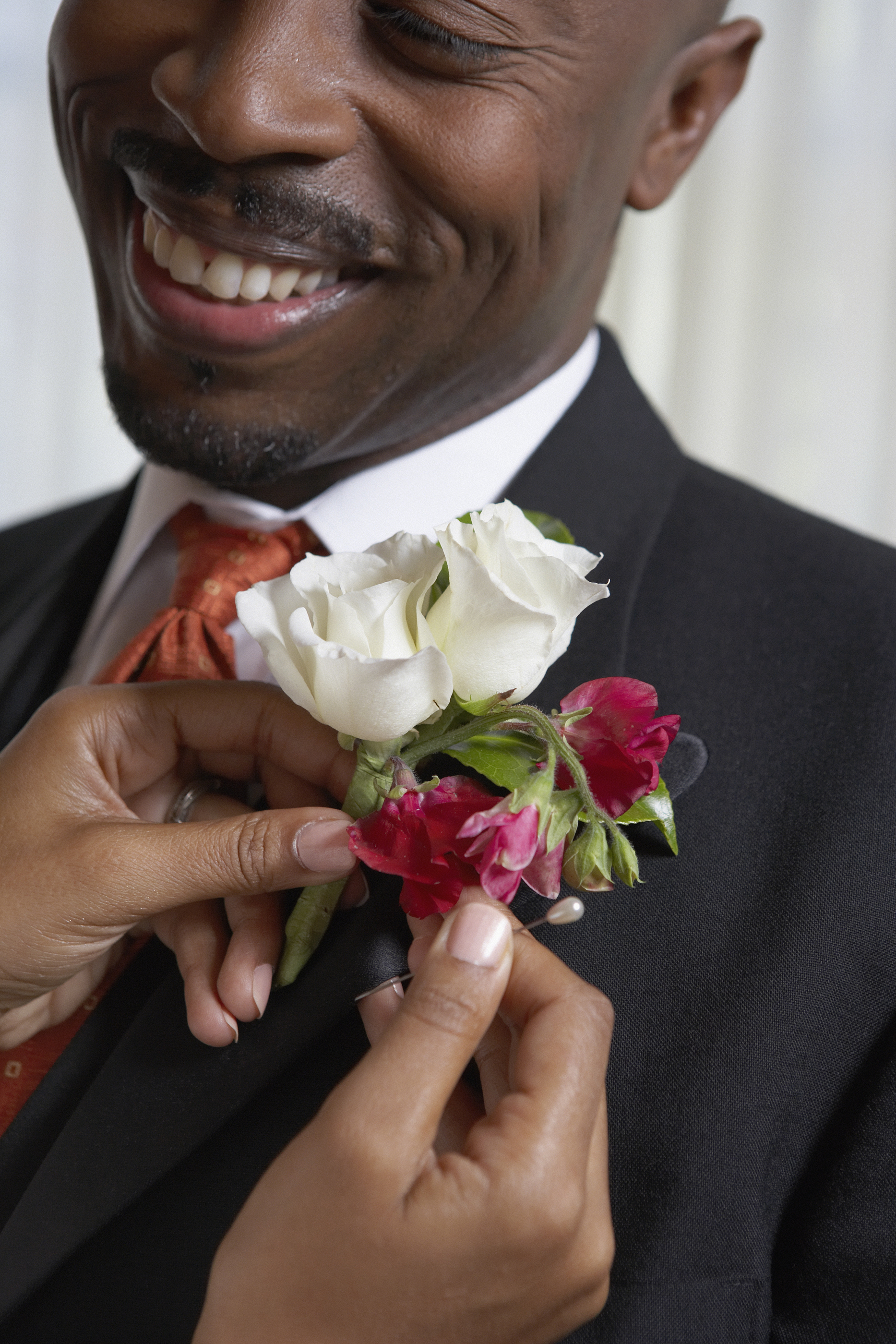 Woman pinning flowers onto man's lapel