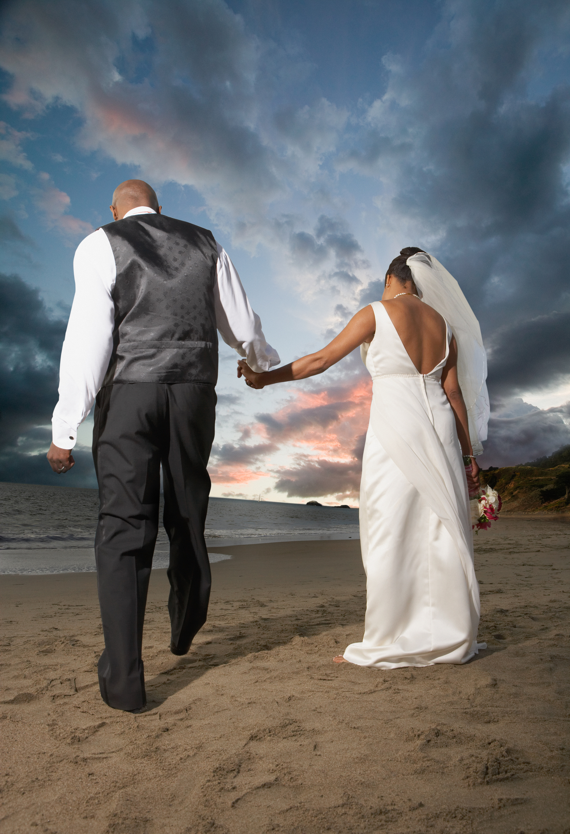 Newlyweds walking on the beach
