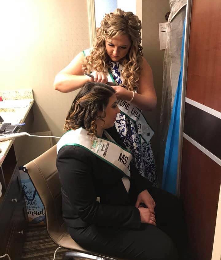 Kayla getting help with her hair from fellow queen, Mariah, at the 2019 National competition
