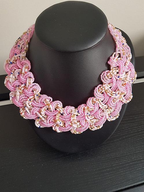 Collier de perles rose pales, blancs, jaunes et bleus tressé et tissé.