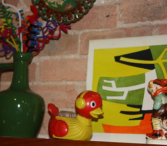 Vintage green vase, vintage red plastic duck with yellow sweater and earmuffs, German Hummel figure of boy and abstract artpiece