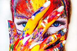 Colorfully painted woman's hand and face