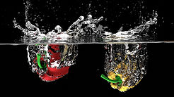 Red and yellow peppers dropping into water