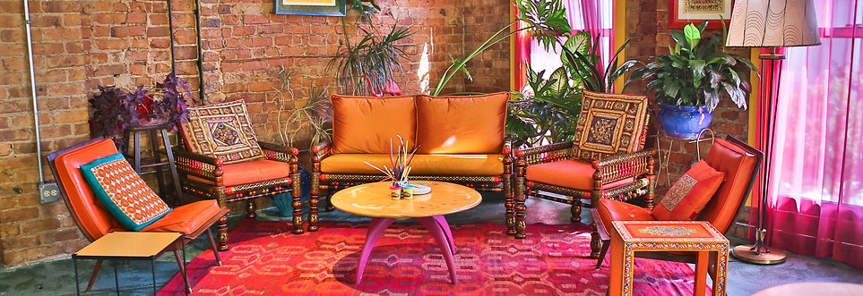 Hand painted Indian loveseat and pair of armchairs with orange cushions, set of 60s vinyl orange curved back chairs, ethnic rug, round vintage coffee table, Indian painted side table