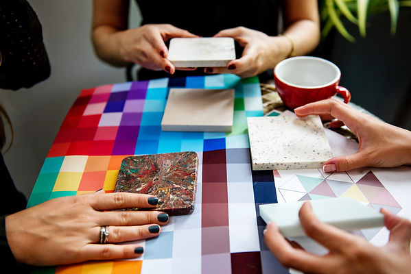 Three women holding various tiles while contemplating a color chart
