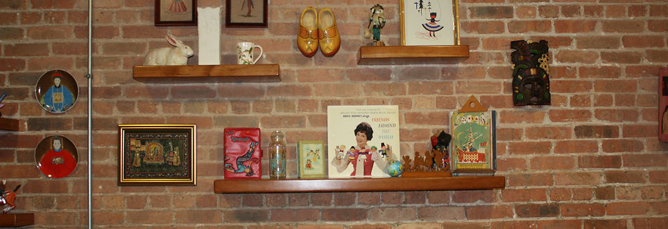 Three reclaimed wood floating bookshelves with a variety of vintage items, pair of wooden Dutch shoes, set of porcelain plates with Chinese emperors, Indian painting