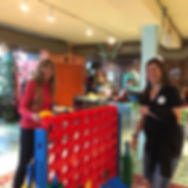 Two women playing giant Connect 4 game