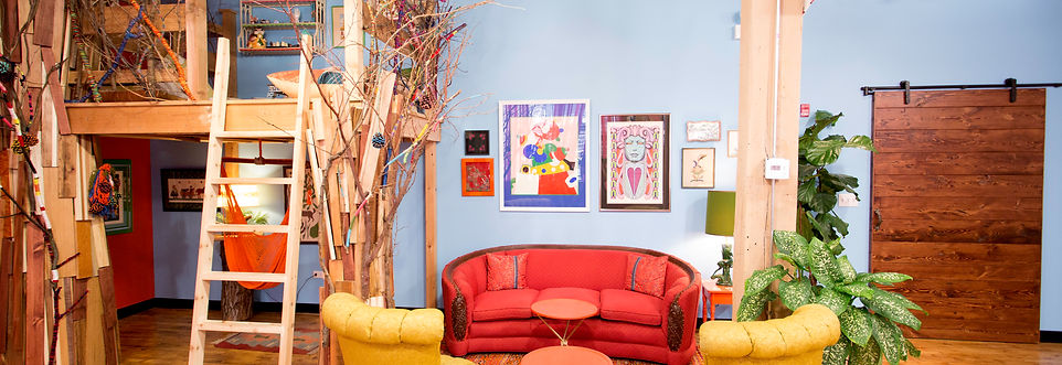 1930s vintage orange couch, pair of mustard yellow armchairs with no arms, orange hammock swing hanging under an indoor treehouse with ladder leading up, vintage artwork on walls