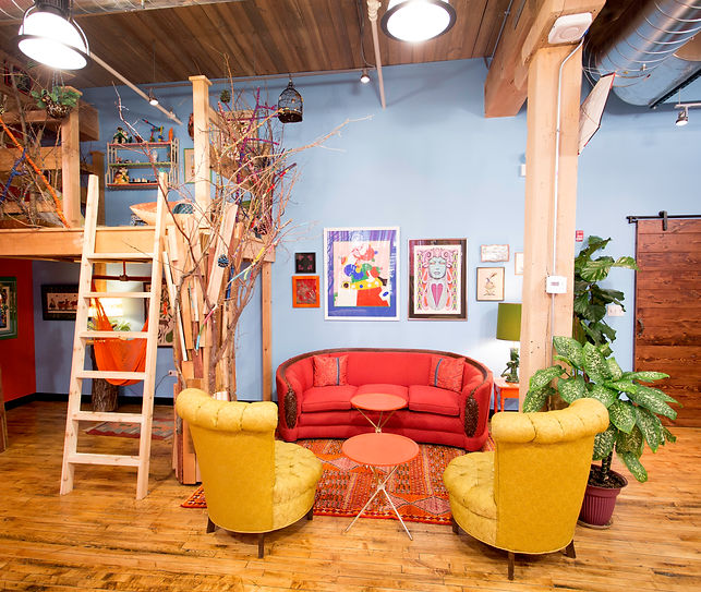 Sunny blue room with indoor tree house, orange hammock swing, vintage 1930s orange couch with mahogany arms, pair of mustard yellow 1940s armchairs, pair of round vintage folding tables, psychedelic artwork, reclaimed wood barn door