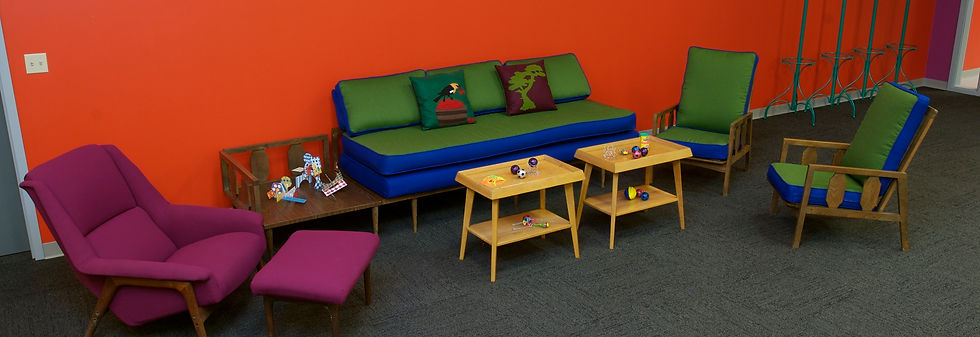 1960s couch with attached side table upholstered in green and bright blue fabric, matching armchair, vintage Mid-century armchair in magenta fabric, pair of mid-century blonde wood side tables with toys