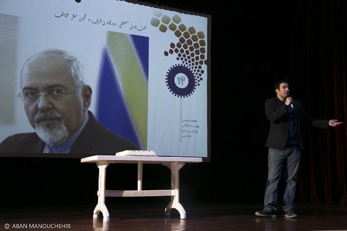 آرش سلیمانی مدیر ارشد ویکی پدیا در حال سخنرانی در کنار عکس جواد ظریف. | منبع: ویکی پدیا