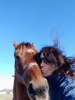 Lara and a brown horse. She is kissing the side of the horse's face.