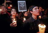 People holding candles and signs