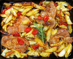 Pork shoulder steaks with paprika, roasted with potatoes, onions, garlic and rosemary