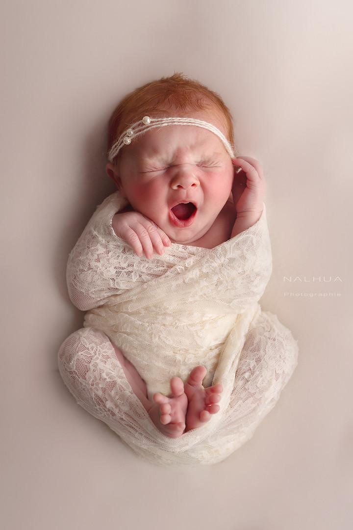 Photographe nouveau né en train de réaliser une séance photo bébé. Photo d'un nouveau né fille au studio à Toulouse.