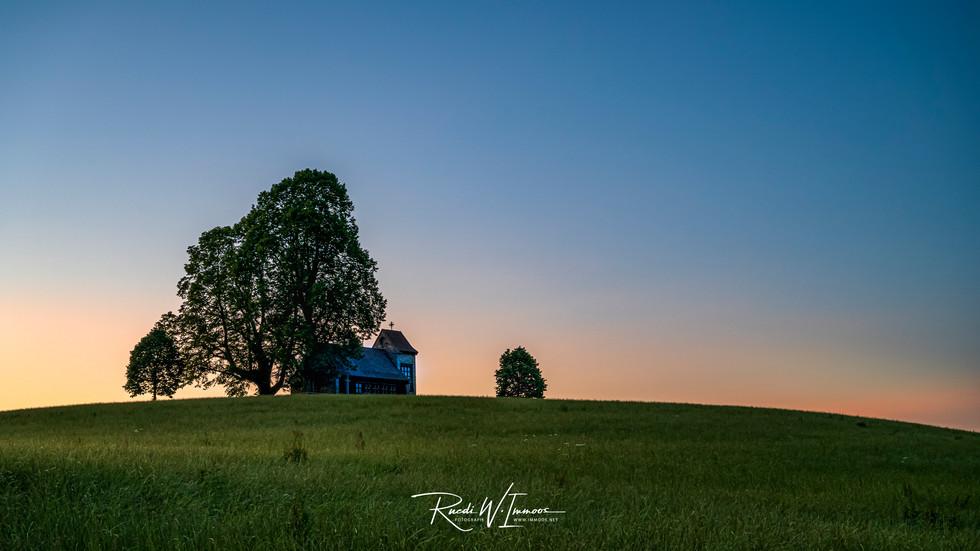 Michaelskreuz Kapelle und Bäume von Osten Abendlicht ohne Wolken rötlich_Z623812-Signet-we