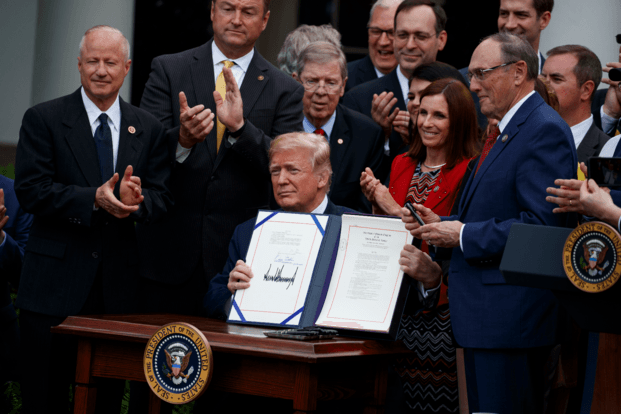 "President Donald Trump shows off the ""VA Mission Act"" during a signing ceremony in the Rose Garden of the White House, Wednesday, June 6, 2018, in Washington. (AP Photo/Evan Vucci)"