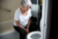 elderly woman sitting on edge of bathtub