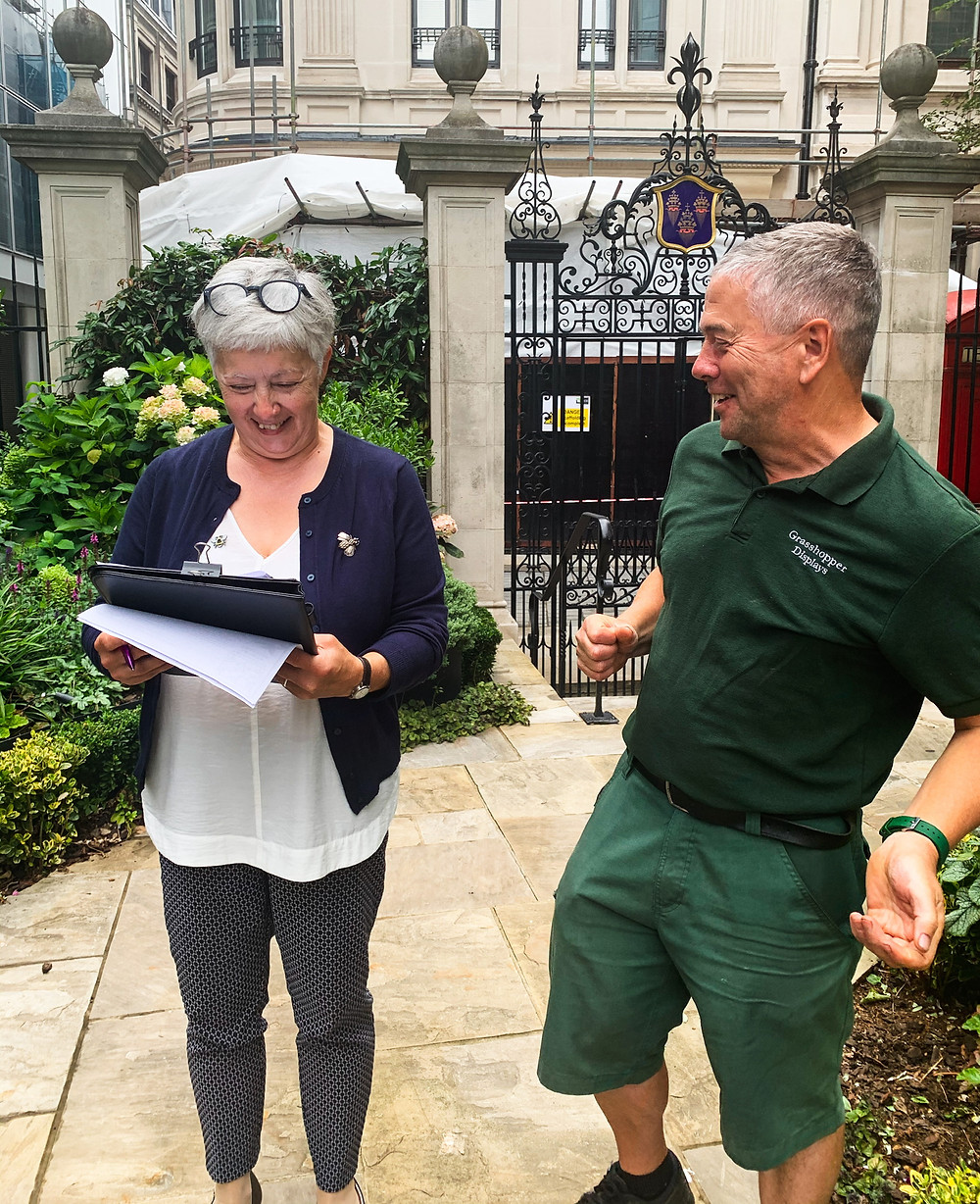 A lady with a clipboard smiling as a gardener celebrates successfully ticking boxes in a garden audit