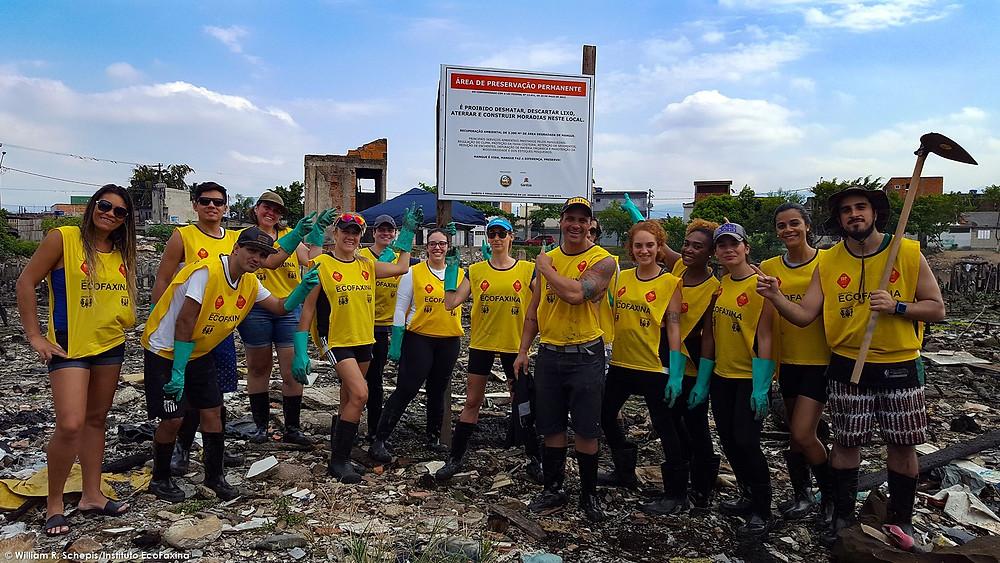 Voluntários posam para foto após a instalação da placa de Área de Preservação Permanente durante a primeira ação de recuperação de área degradada de mangue no rio dos Bugres, realizada no dia 22/4.
