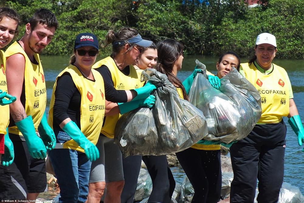 Voluntários retiram sacos de lixo cheios de plástico e isopor coletados no rio São Jorge, em Santos.
