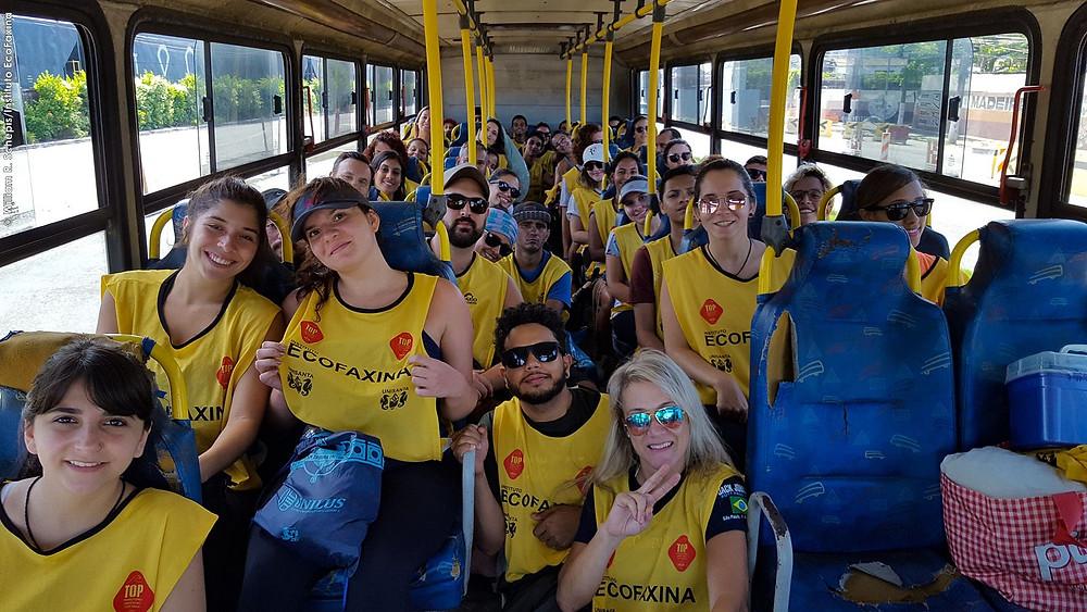 Voluntários posam para foto no ônibus a caminho do manguezal.