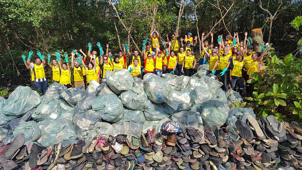 Voluntários posam para foto com os resíduos coletados no manguezal de Santos.