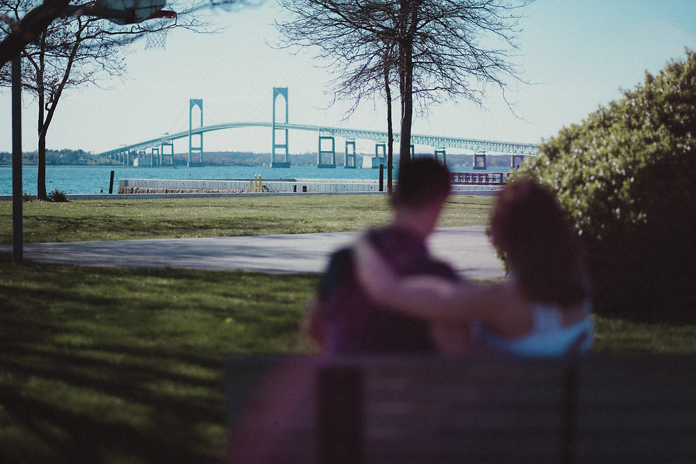 couple's engagement session overlooking the Newport Bridge in Rhode Island on Goat Island