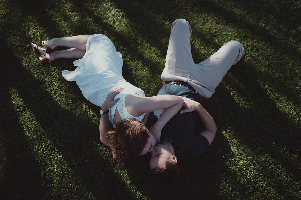 couple's engagement photo shoot in Newport, Rhode Island laying on the grass