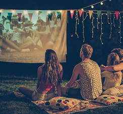 Outdoor Movie projected on a screen with four people sitting on a blanket