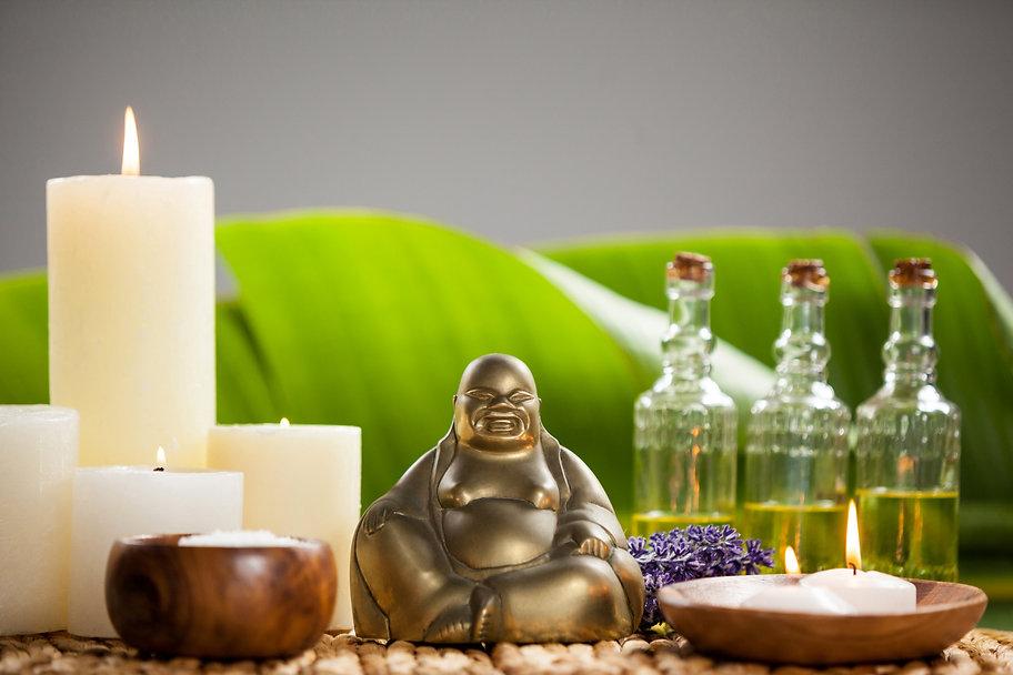 laughing-buddha-figurine-lit-candle-mass