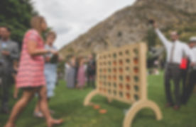 People smiling at a wedding playing giant connect 4 or four in a row