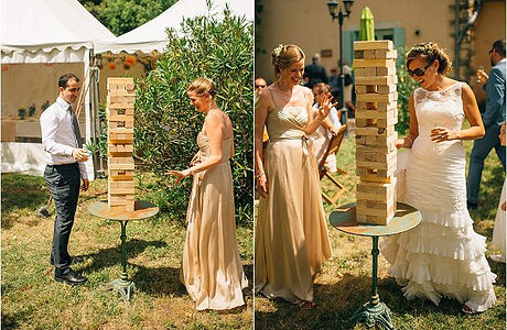Bride, groom and bridesmaid lauplaying Giant Jenga at a wedding