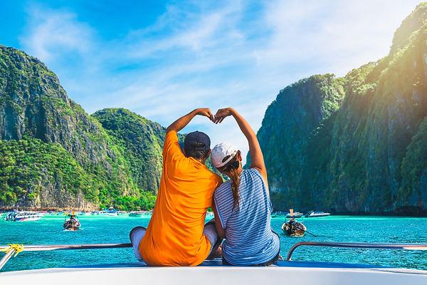 Happy couple traveler doing heart shape joy relaxing on boat Maya beach, Krabi Phuket, Tra