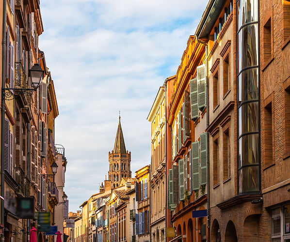 Rue du Taur in the historic center of Toulouse, and the bell tower of Saint Sernin in the