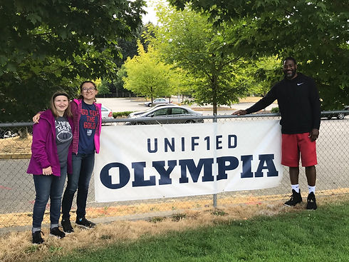 """Three individuals are standing together in front of a banner that says """"Unified Olympia."""" One the left side are two white females. On the right side is one african american male. This is Megan, Natalie, and Antonio."""