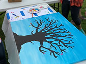 There is a painting lying on the table. The painting has a blue background and a large tree on it.