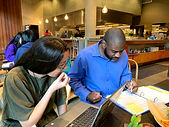 This is a picture of Natalie and Antonio (Thurston County Inclusion's Executive Directors) working hard at a table. Natalie has a computer open in front of her and Antonio is reading a binder.