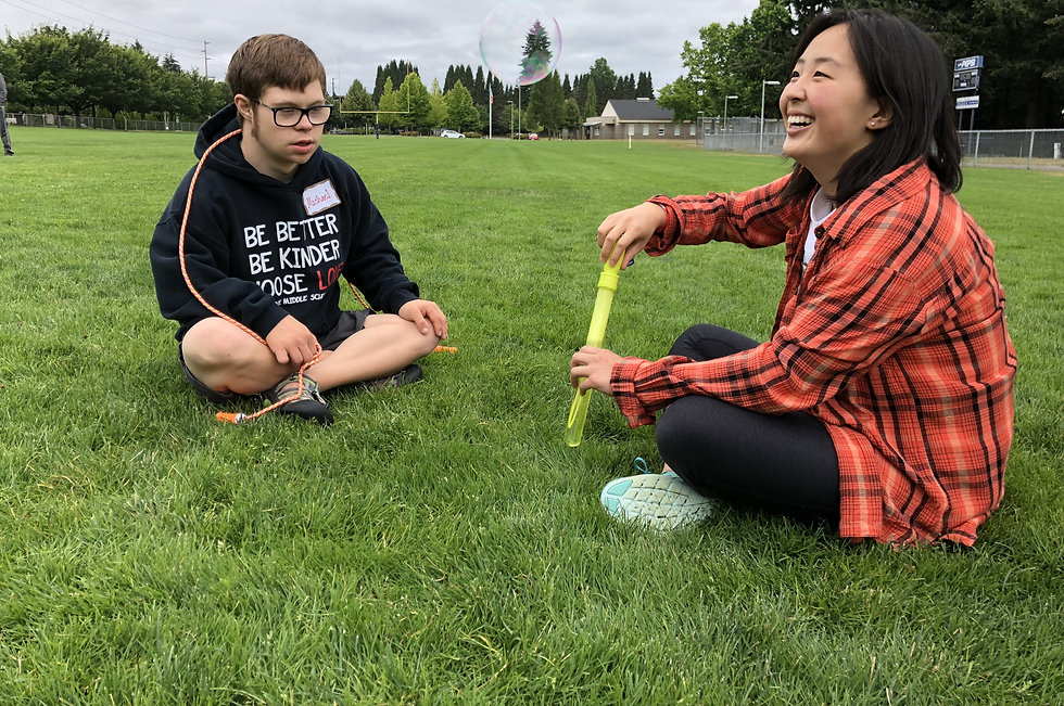 Two individuals sit on a field blowing bubbles. On the right, is a disabled white male and on the left is a nondisabled, asian female.