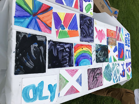 This is a sideways picture of canvas paintings. There are several all black paintings and a rainbow painting among other colors.